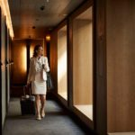businesswoman-with-suitcase-at-hotel-corridor