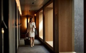 Smiling businesswoman with suitcase walking in corridor at hotel